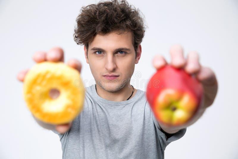 Человек держа яблоко и донут стоковые фотографии rf