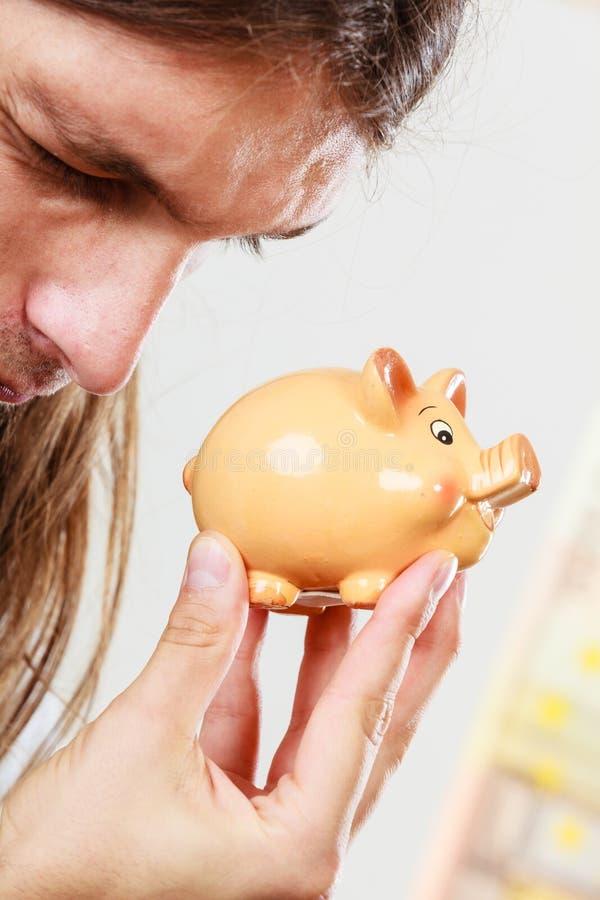 Человек держа piggybank moneybox стоковое фото