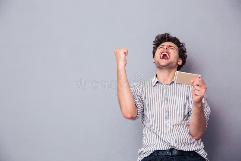 Человек держа smartphone и празднуя его успех стоковая фотография rf