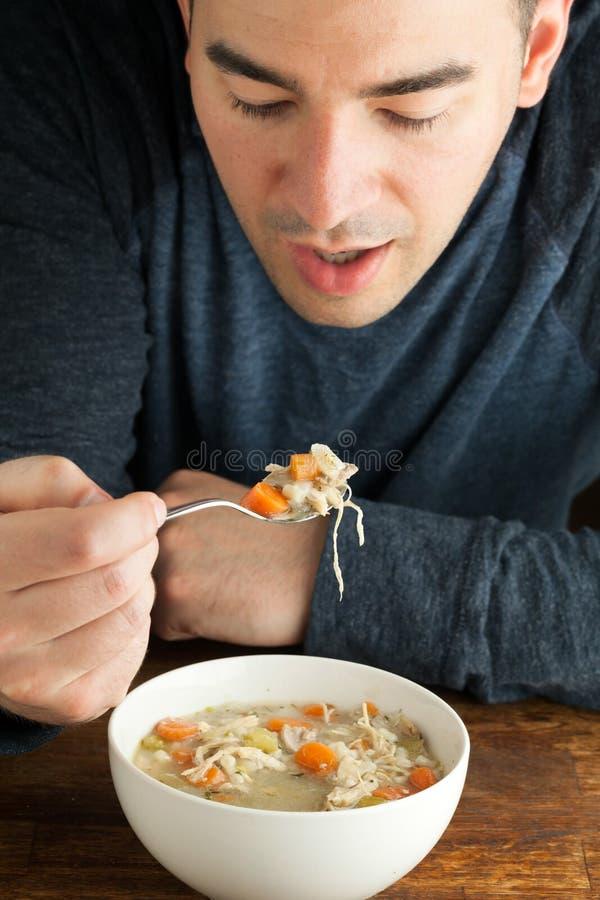 Человек есть домодельный куриный суп стоковые изображения rf
