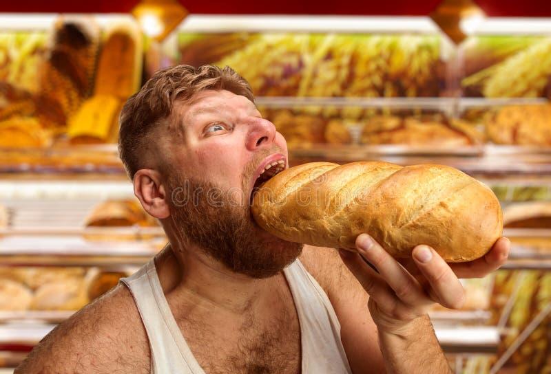 Человек есть хлеб в магазине стоковое изображение rf