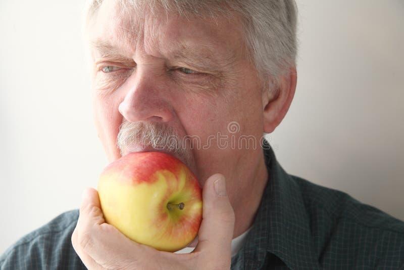 Человек ест яблоко стоковые фото