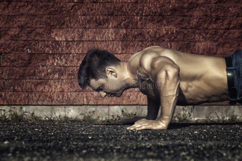 Человек детенышей подходящий отжат и показан мышцы стоковые фотографии rf