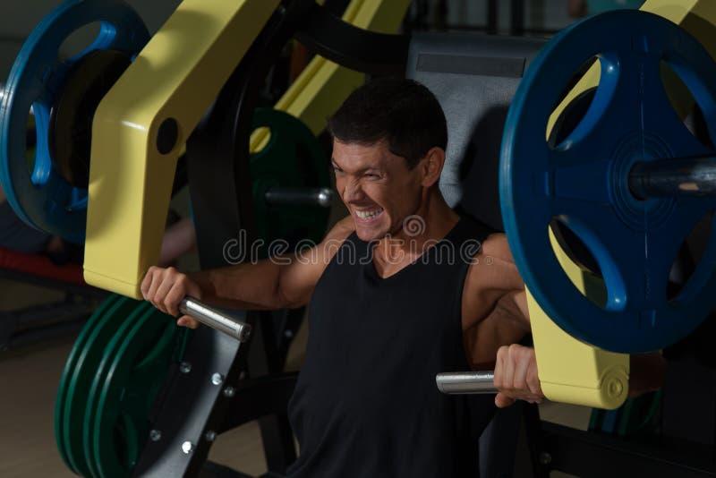 Человек делая тренировку прочности на машине тренировки стоковые изображения