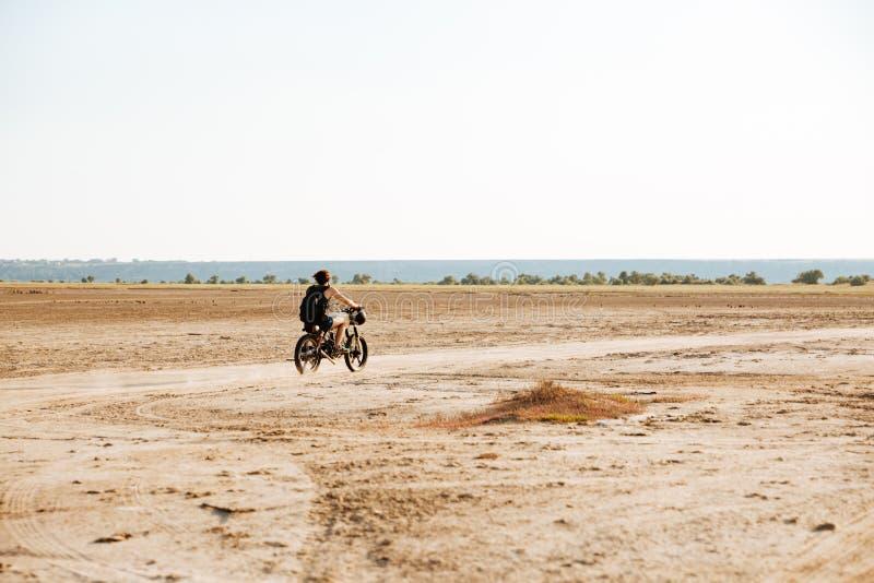 Человек едет его мотоцикл через пустыню стоковое фото