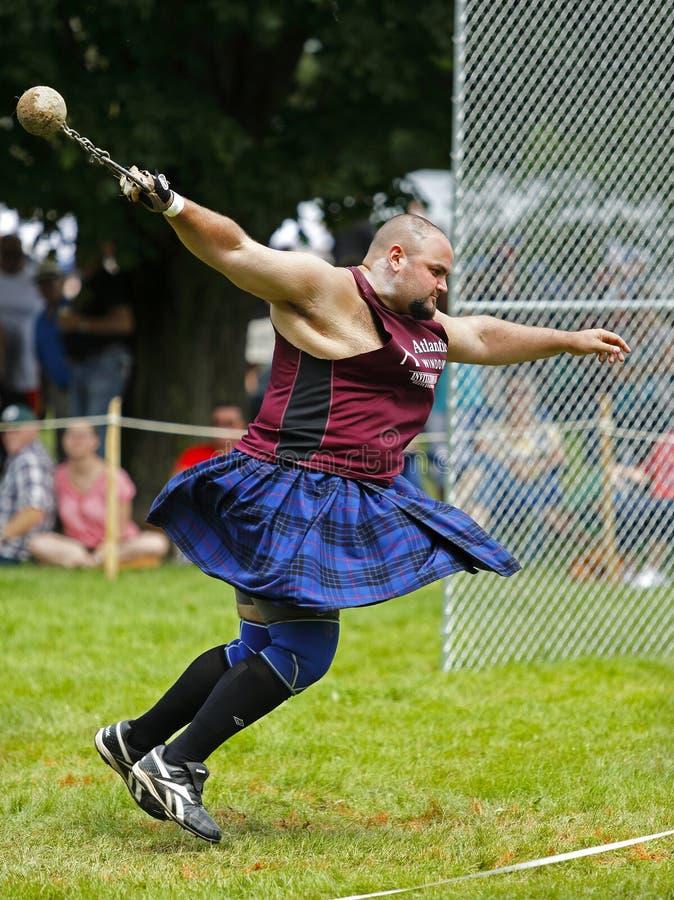 Человек закрутки веса игр гористой местности стоковые фото
