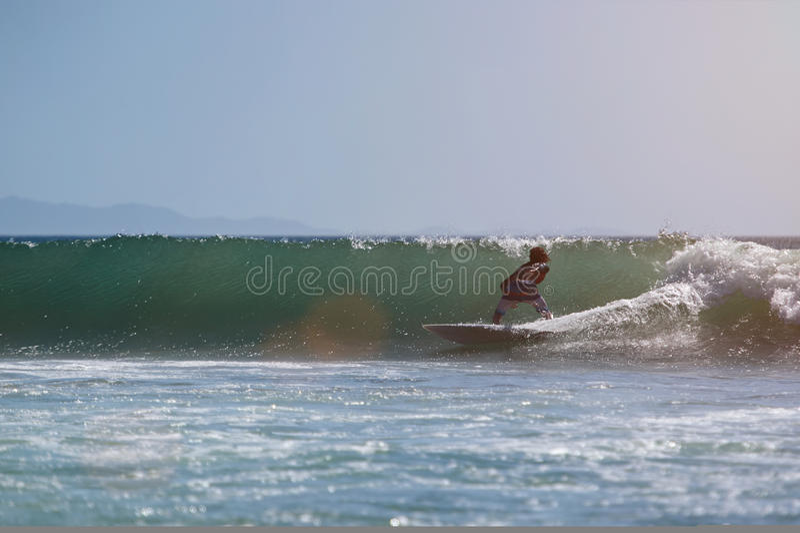 Человек занимаясь серфингом на волне Тихого океана стоковое изображение