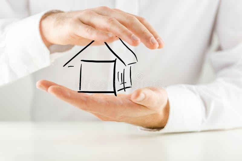 Человек защищая дом с его руками стоковые фото