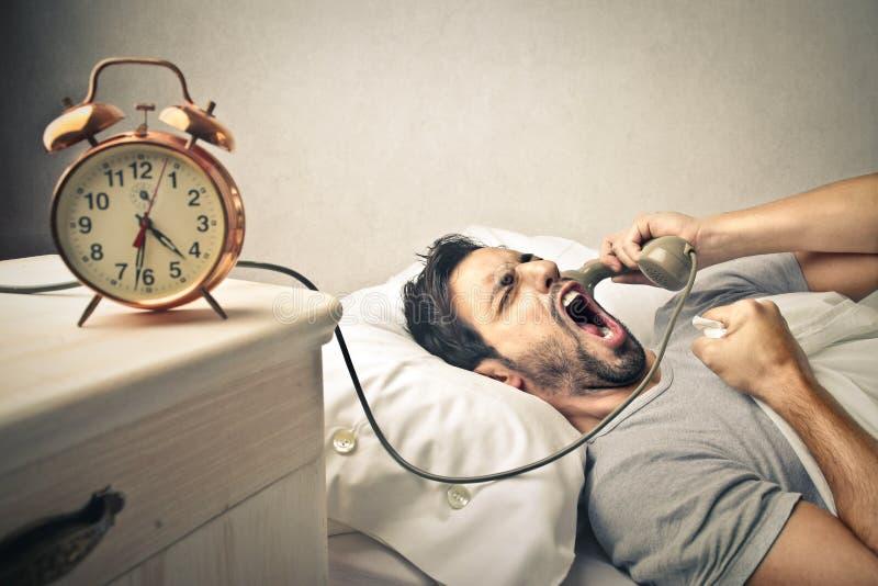 Человек зевая на телефоне стоковое фото