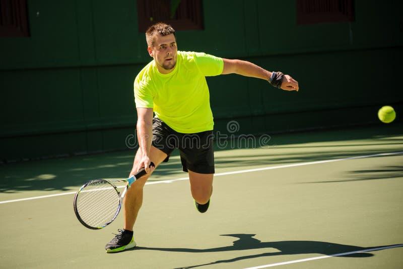 Человек играет теннис в яркой ткани стоковое изображение rf