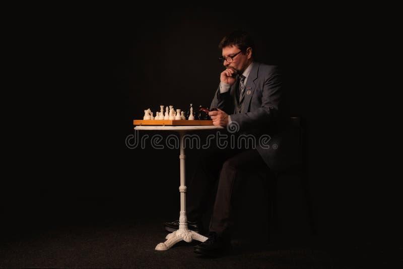 Человек играет шахмат и курит трубу на темной предпосылке стоковая фотография