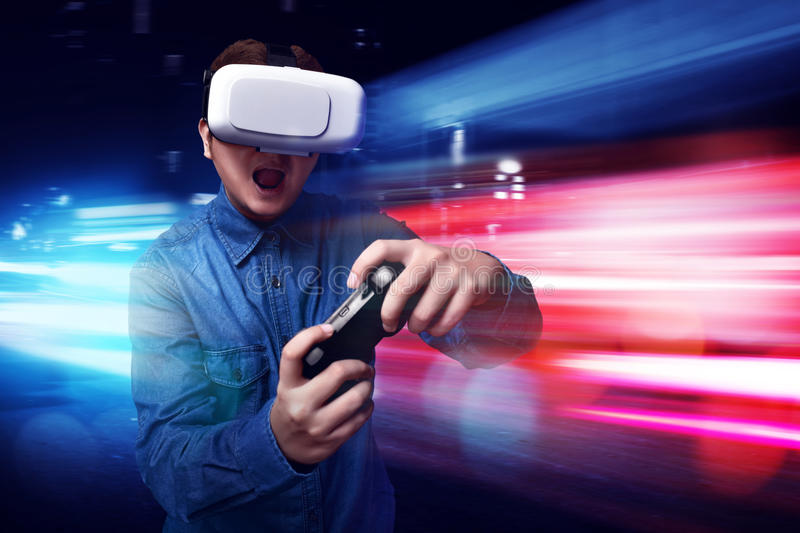 Человек играя видеоигры нося изумлённые взгляды vr стоковое фото rf