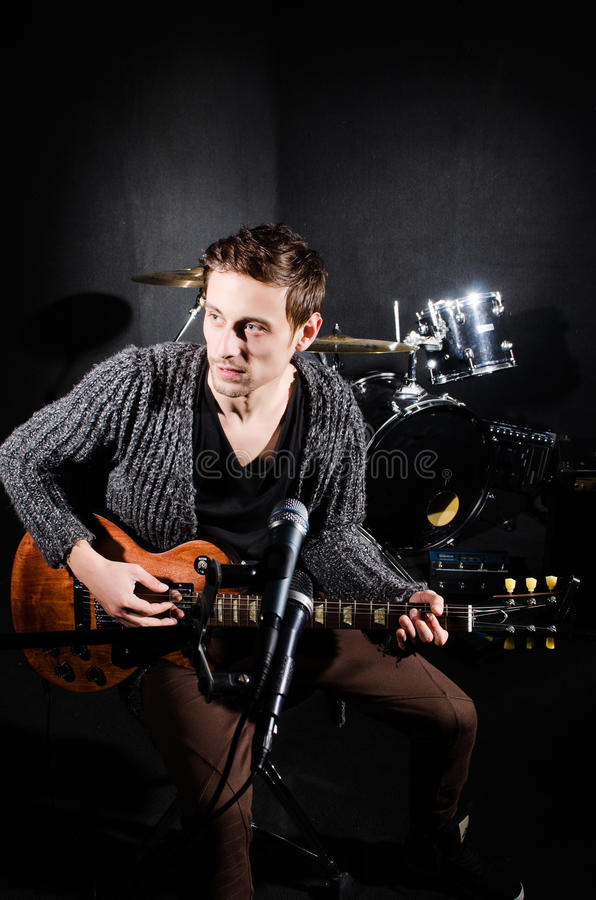 Человек играя гитару в темной комнате стоковая фотография rf