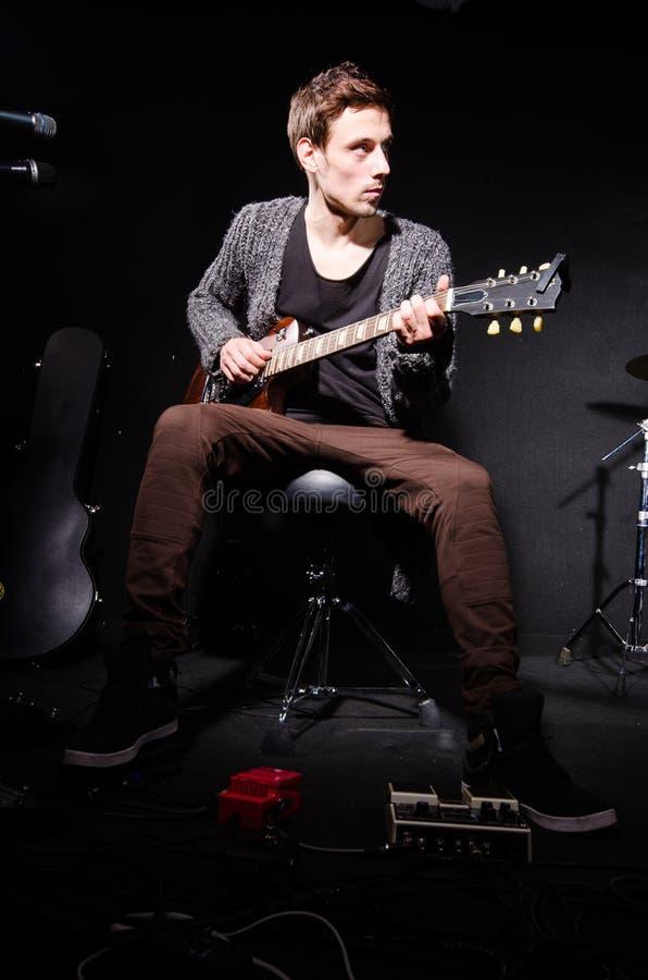 Человек играя гитару в темной комнате стоковые изображения rf