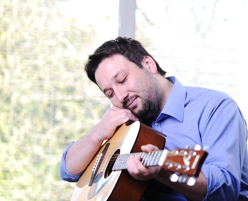 Человек играя гитару крытую стоковая фотография