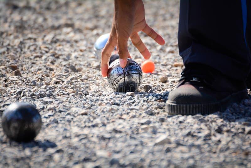 Человек играя игру в петанки, шарики на том основании стоковые изображения rf