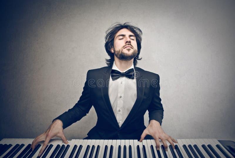 Человек играя рояль стоковое изображение
