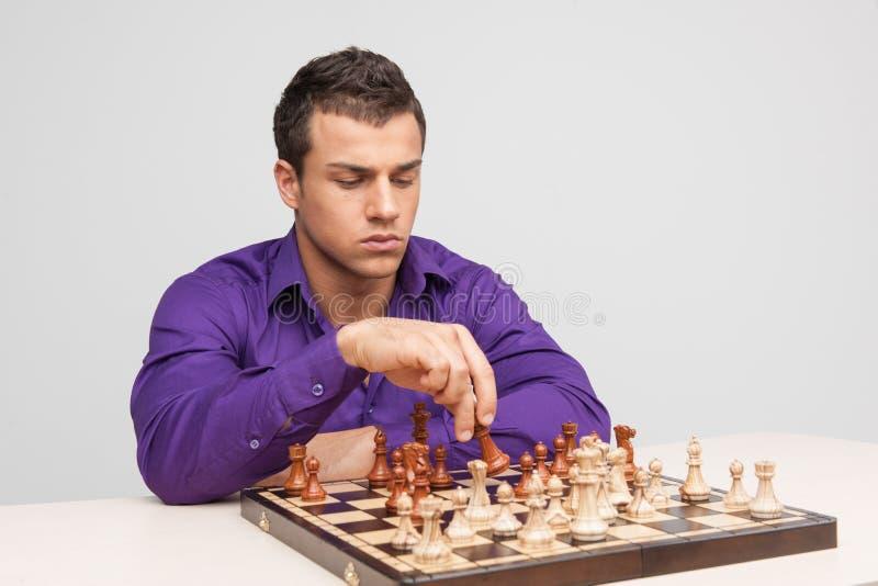 Человек играя шахмат на белой предпосылке стоковое фото