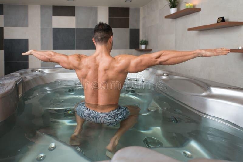 Человек изгибая мышцы в курорте джакузи стоковые фотографии rf