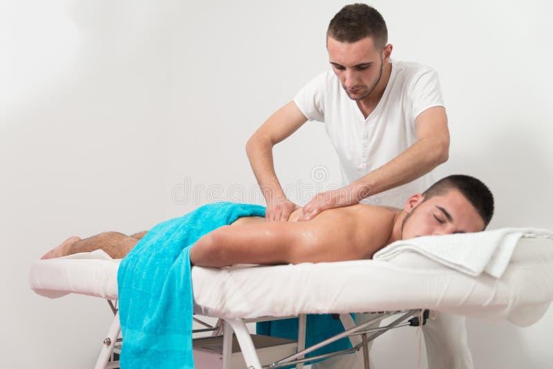 Человек имея задний массаж в спа-центре стоковая фотография rf
