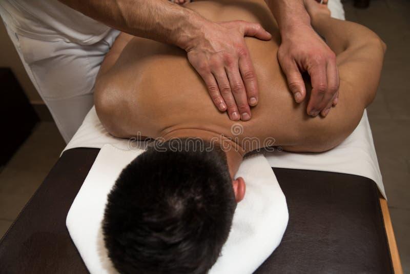 Человек имея задний массаж в спа-центре стоковое фото rf