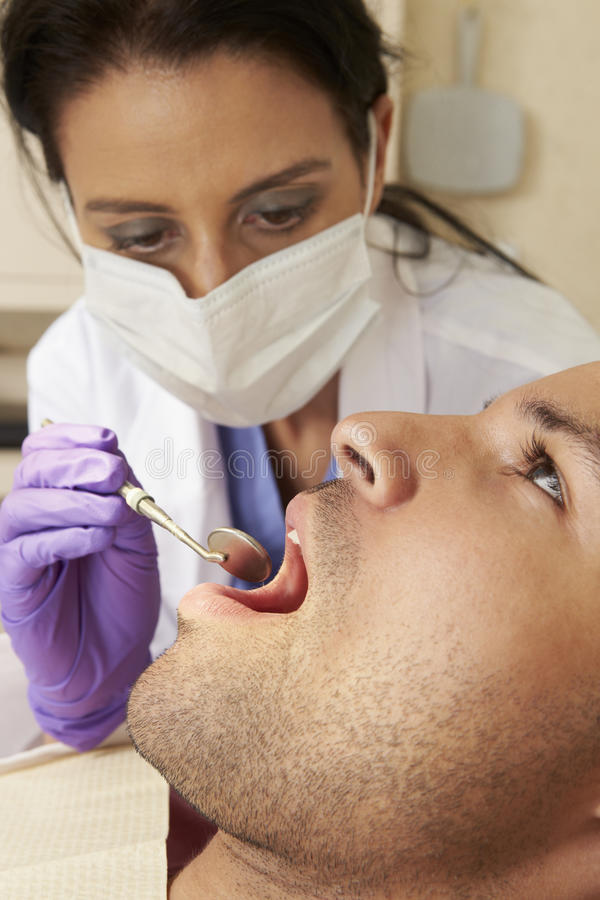 Человек имея проверку вверх на хирургии дантистов стоковая фотография