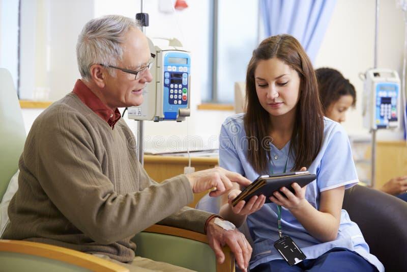 Человек имея химиотерапию при медсестра используя таблетку цифров стоковое изображение