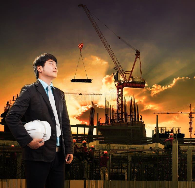 Человек инженерства и шлем безопасности стоя против constru крана стоковая фотография
