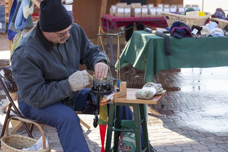 Человек использует машину для того чтобы сделать носки шерстей на под открытым небом рынке стоковое изображение rf