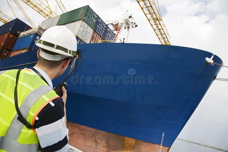 Человек используя звуковое кино Walkie на контейнерном терминале стоковое фото