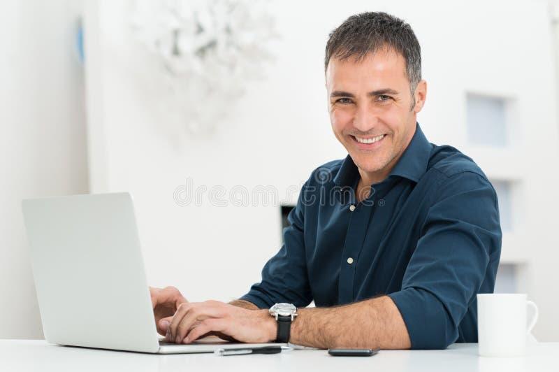 Человек используя компьтер-книжку на столе стоковое изображение rf