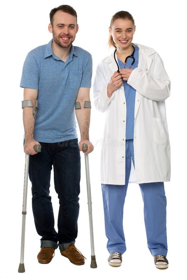 Человек используя костыли, рядом с дружелюбным врачем стоковое фото