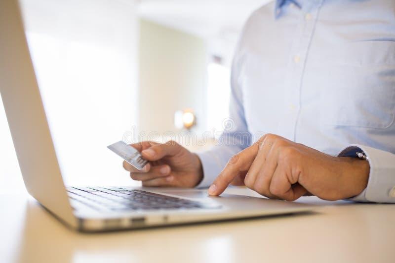 Человек используя кредитную карточку и компьтер-книжку, ходя по магазинам на line.indoor стоковая фотография