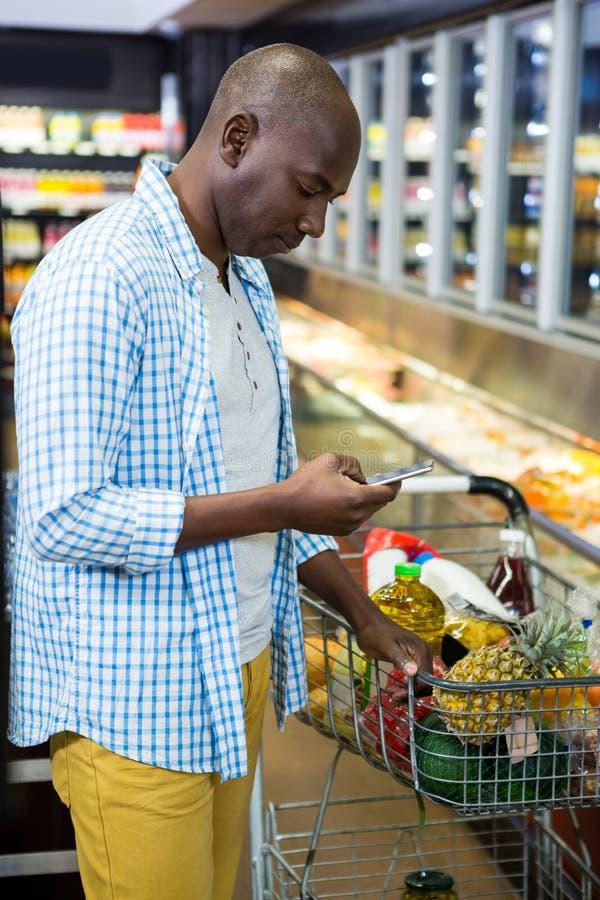 Человек используя мобильный телефон в разделе бакалеи пока ходящ по магазинам стоковые фотографии rf