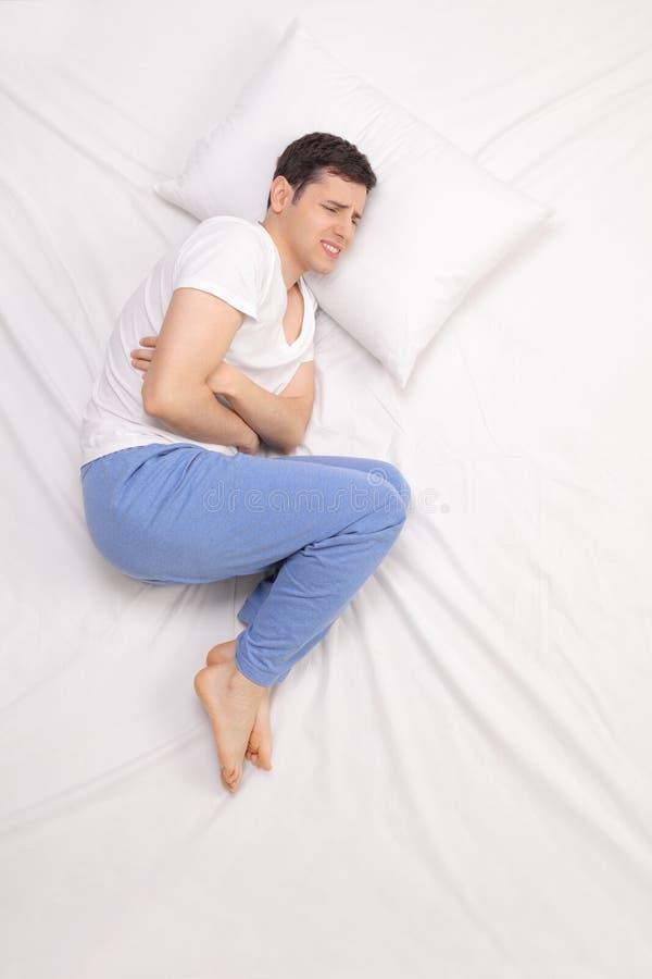 Человек испытывая боль в животе стоковое изображение rf