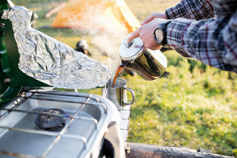 Человек лить горячий чай в чашке пока располагающся лагерем стоковое изображение