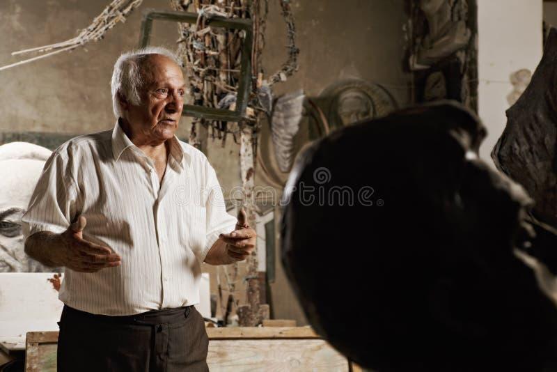 Человек и голова скульптуры стоковое фото
