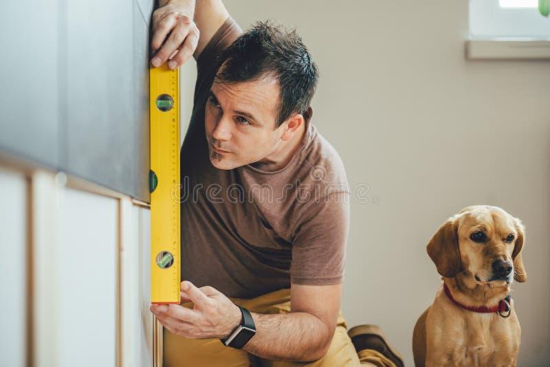 Человек и его собака делая ремонтные работы дома стоковые фото