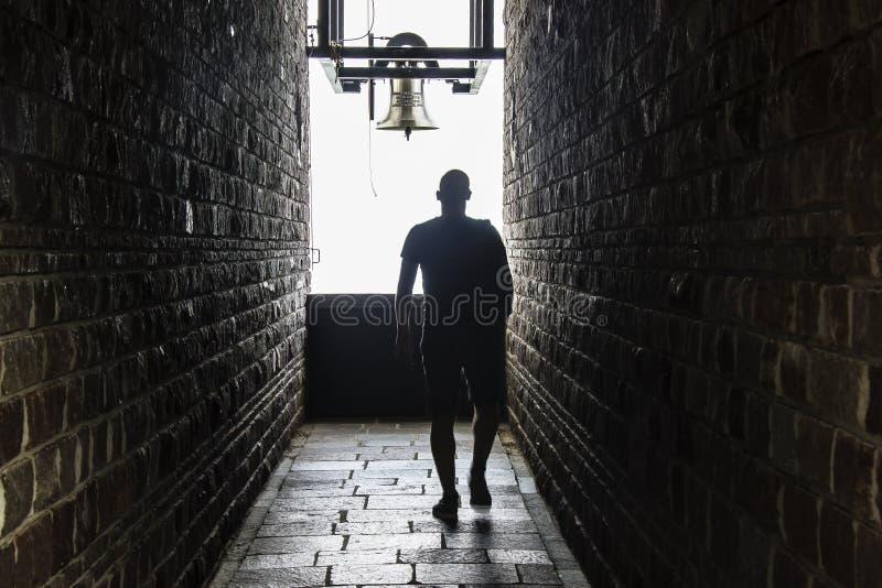 Человек идет в темный тоннель, но выставки света в конце стоковая фотография