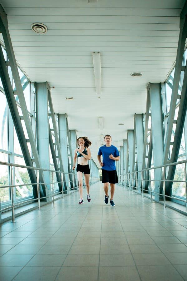 Человек и женщина бежать в современном строительстве моста стоковая фотография