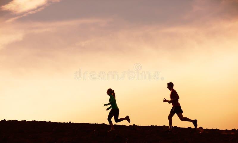 Человек и женщина бежать совместно в заход солнца стоковые изображения