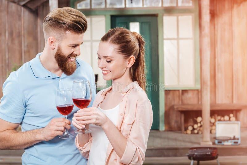 Человек и женщина обнимая и держа вино в рюмках стоковые фото