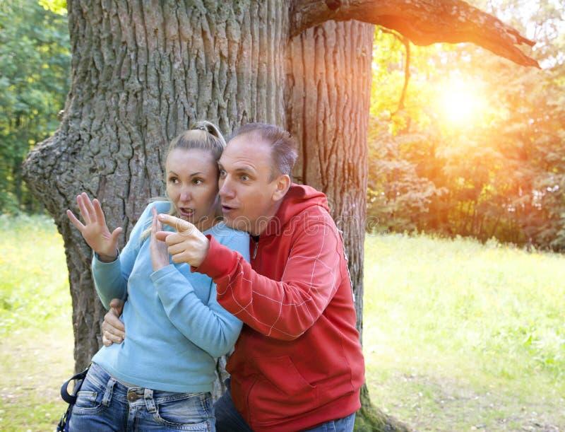 Человек и женщина около дуба в летнем дне что-то были увидены в сторону и посмотрели вспугнутыми и с изумлением стоковая фотография