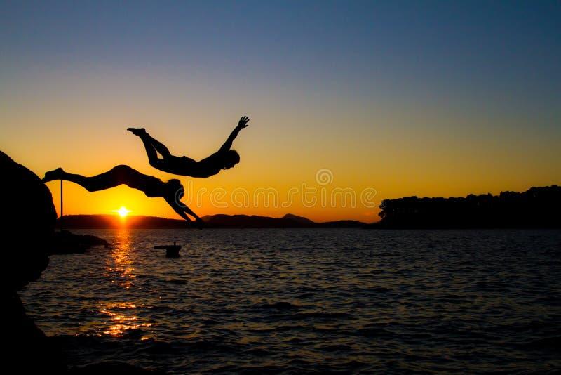 Человек и женщина скачут в воду на заходе солнца стоковое изображение