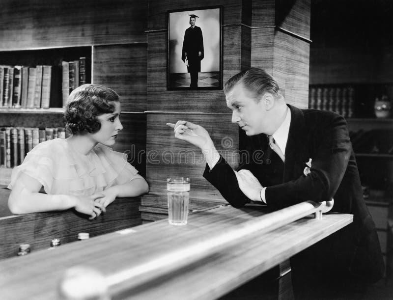 Человек и женщина стоя совместно на счетчике и говорить бара (все показанные люди более длинные живущие и никакое имущество не су стоковое фото