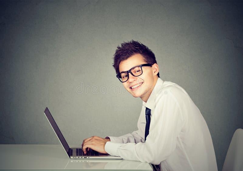 Человек идиота технологии работая на его компьтер-книжке стоковое фото