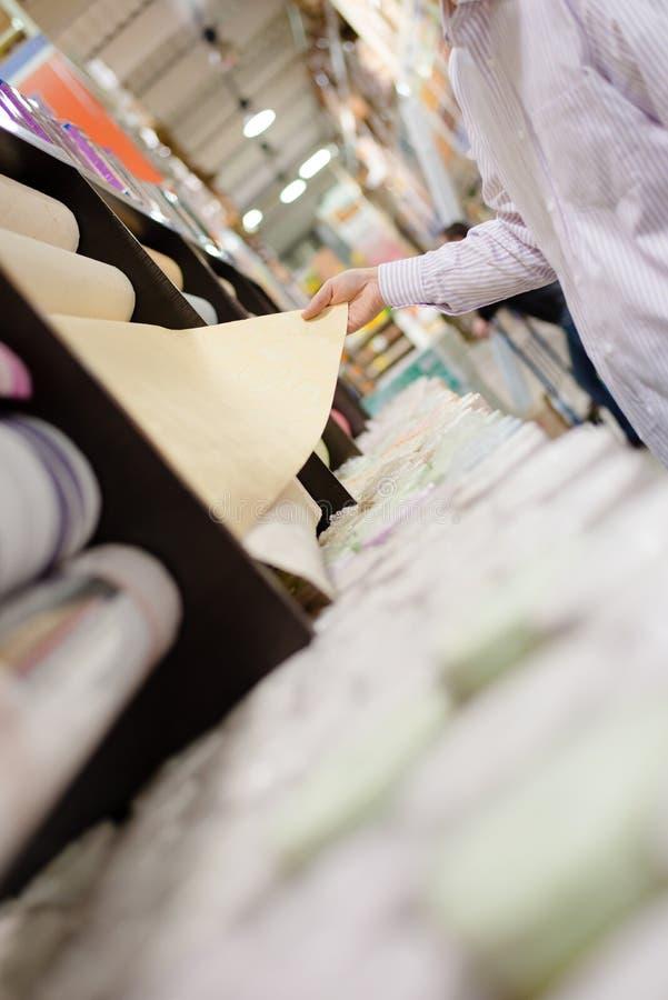 Человек или женщина смотря и выбирая дизайн для покупая обоев в крупном плане магазина DIY в наличии на полке дисплея супермаркет стоковая фотография