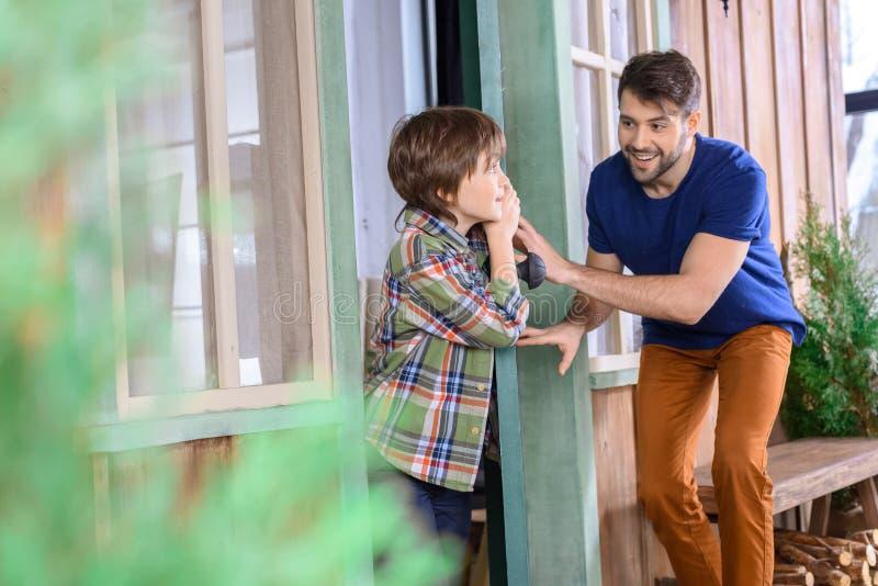 Человек и мальчик играя прятк дома стоковое фото