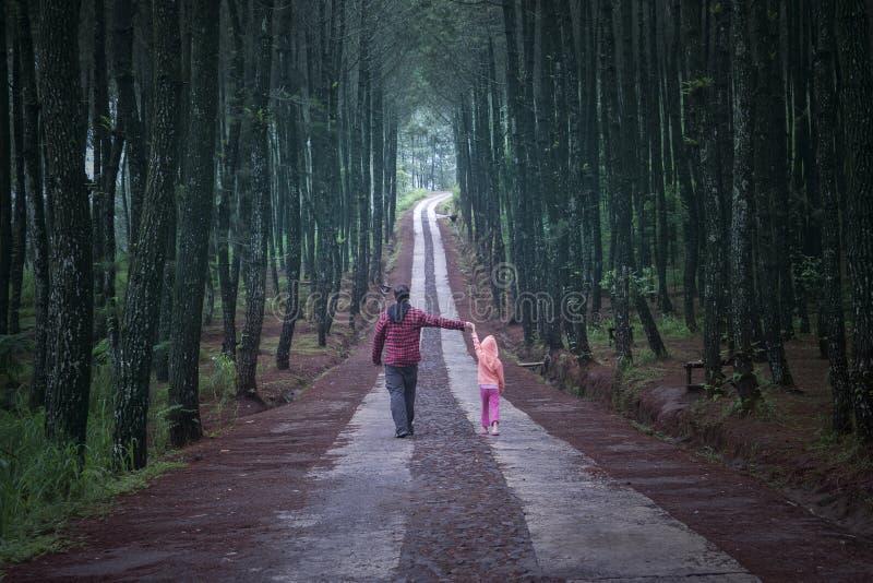 Человек и дочь идя в лес стоковые фотографии rf