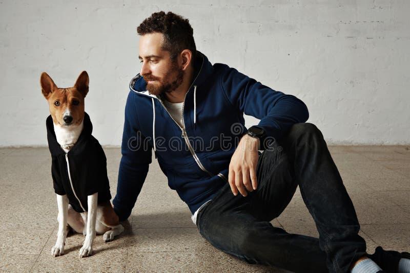 Человек и собака в соответствуя hoodies стоковое фото